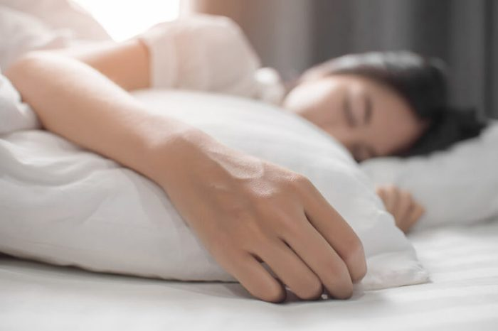 Woman sleeping on her side in a white bed