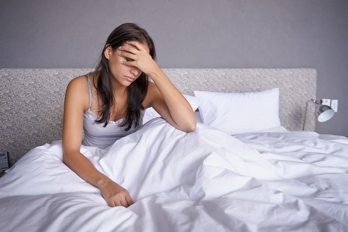exhausted woman sitting in bed