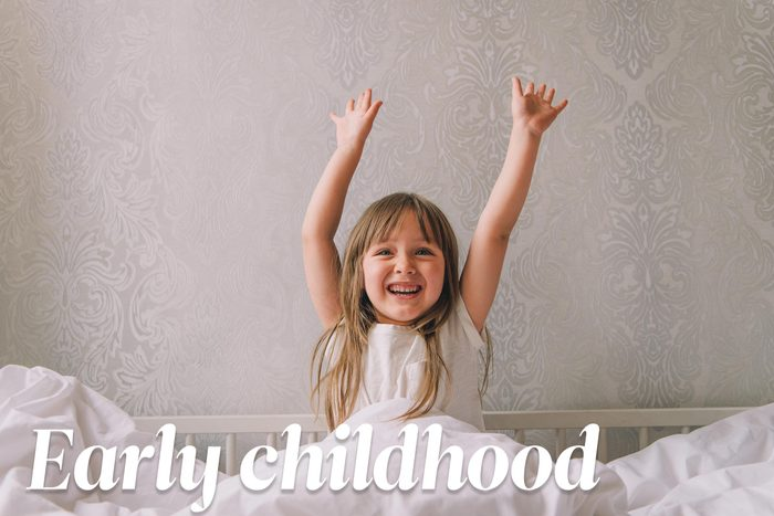 happy young girl with her hands up in the air