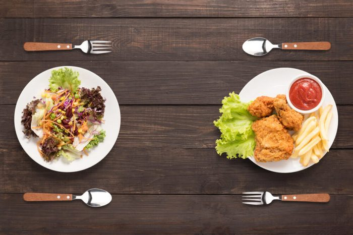 two plates: one with salad and one with fried chicken with French fries