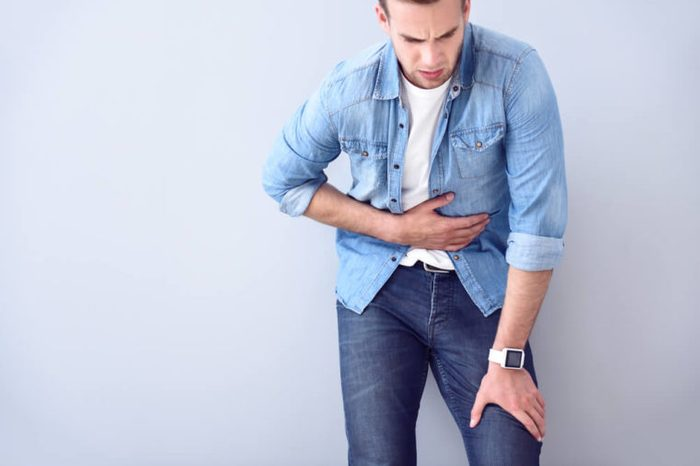 Man in a jean shirt holding his stomach as if having a stomachache.