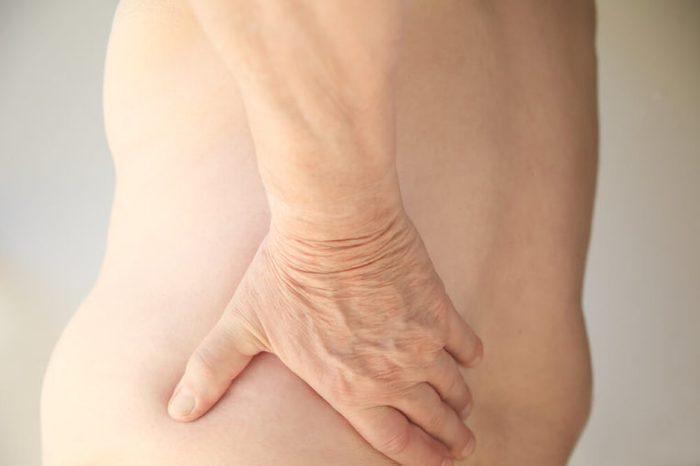 A shirtless man has his hand on his sore back.