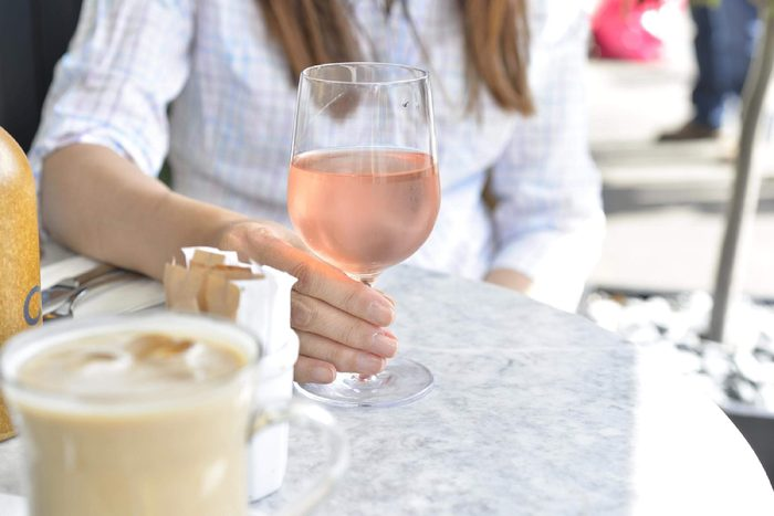 Woman's hand holding a glass of rose wine