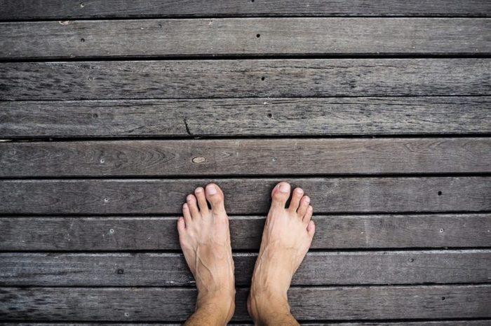 Bare feet standing on wooden floor