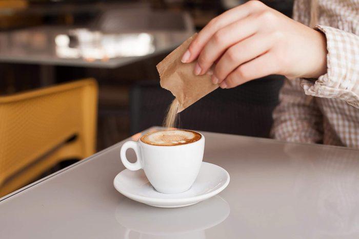 Woman adding sugar in coffee