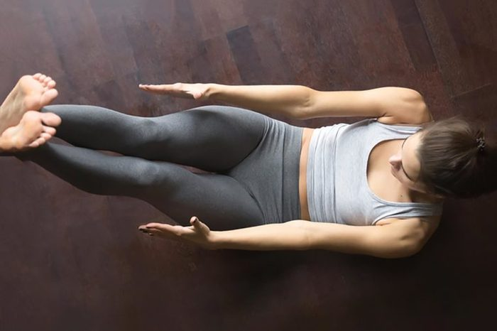Female working out at home, doing fitness exercise on floor, Paripurna Navasana for upper and lower abs, Full Boat pose. Core training. Top view. Full length