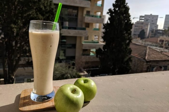 tall glass with smoothie next to two green apples on a ledge outdoors