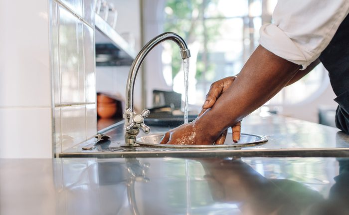 Close up of chef washing his hands in commercial kitchen. Man washing hands in a sink with tap water.