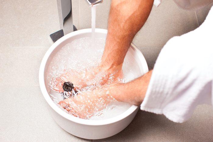 Man having hydrotherapy water footbath in spa setting