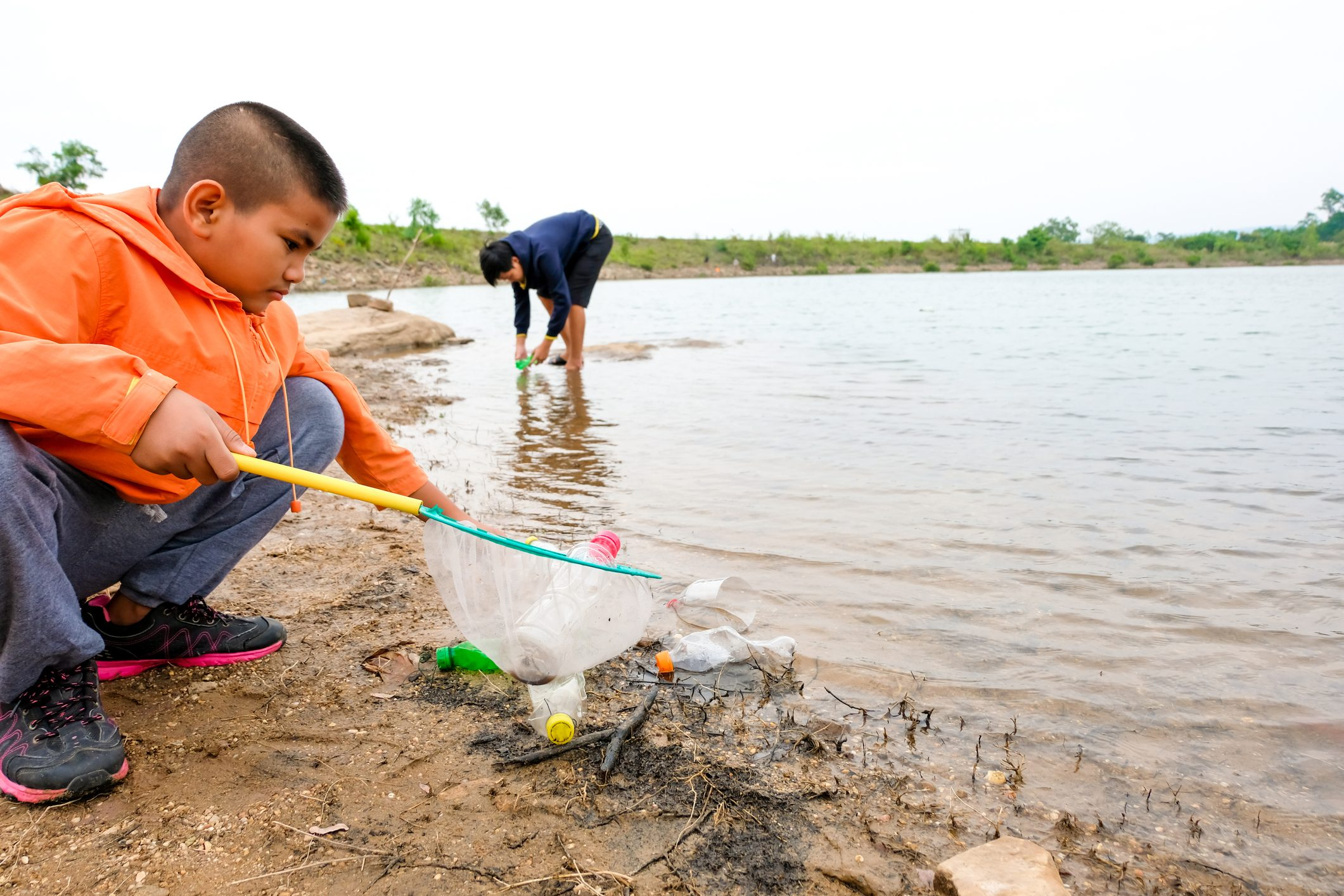 young boy removing trash from river