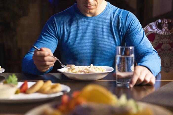 cropped shot of man eating at table