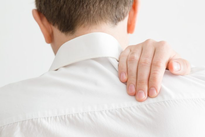 rear view of man holding shoulder from pain