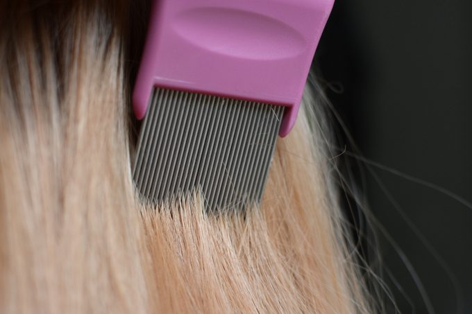 combing through hair with lice comb