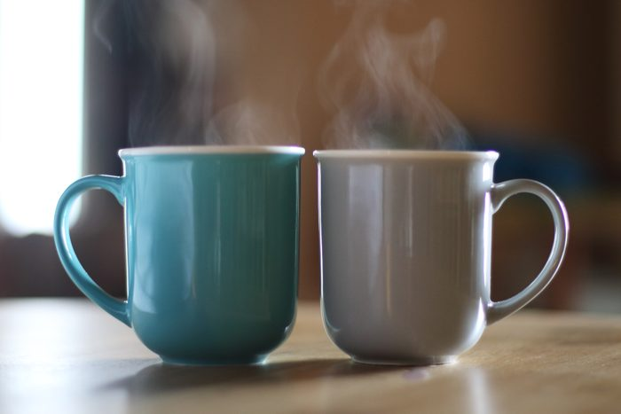 two cups of hot coffee on table