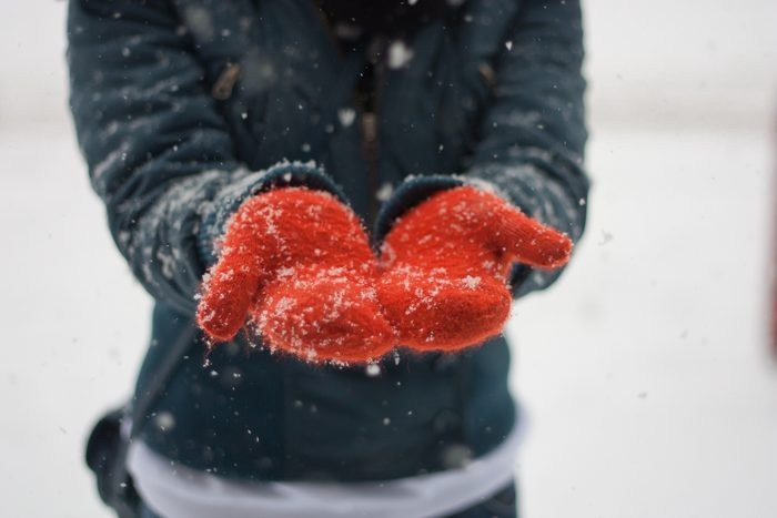 cropped shot of hands wearing mittens in the snow