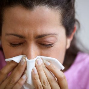 close up of woman blowing nose into tissue