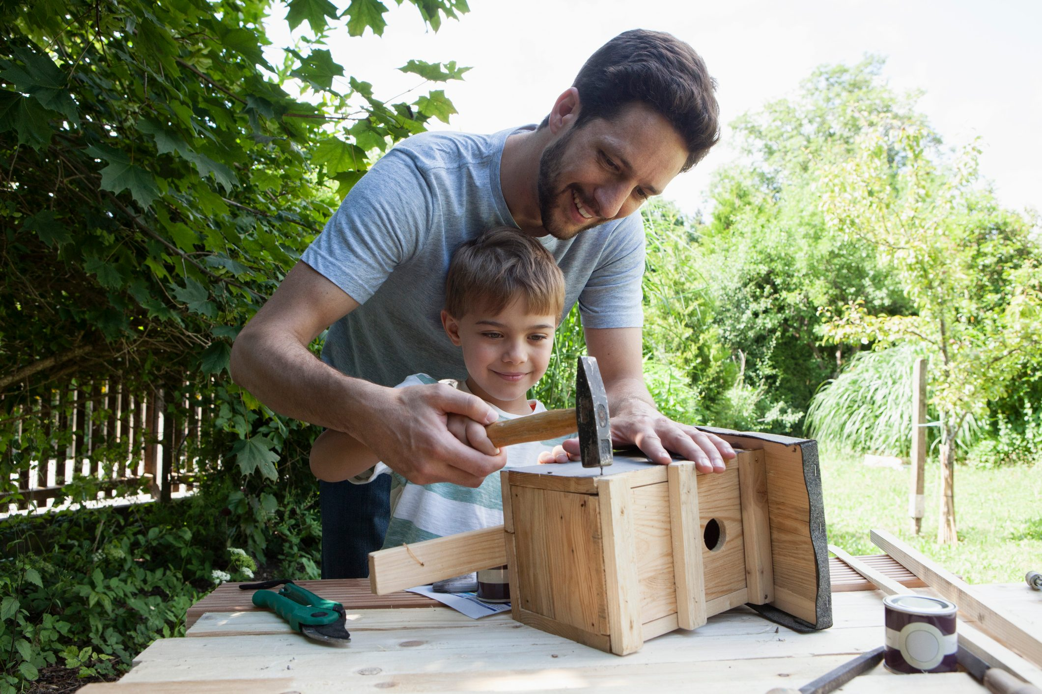 father and son building a birdhouse together