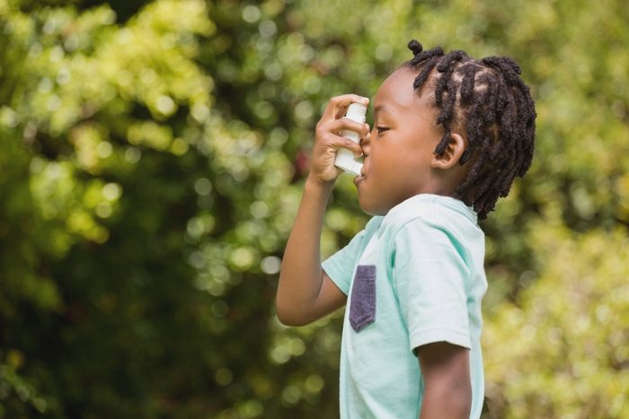 profile view of child using asthma inhaler
