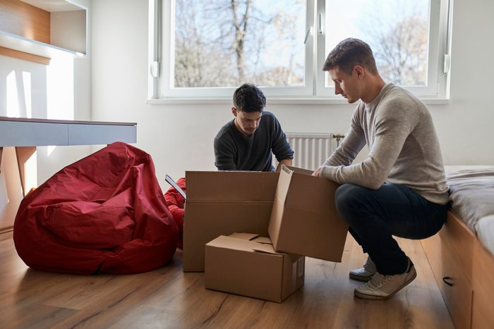two young men unpacking boxes at college