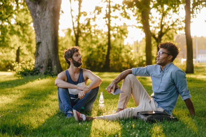 two men sitting in the park having a conversation