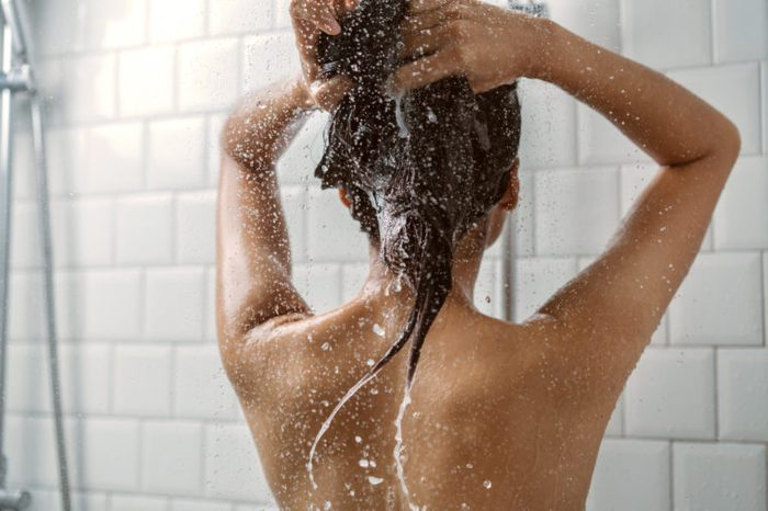 woman showering and washing her hair