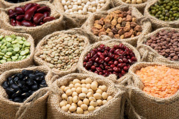 Multicolor dried legumes in burlap sacks
