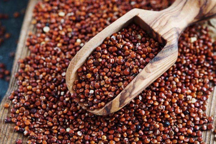 Seeds of red quinoa in wooden scoop