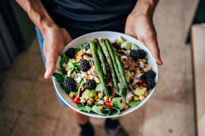 Man holding plate full of vegetarian salad with vegetables and fruits, and berries