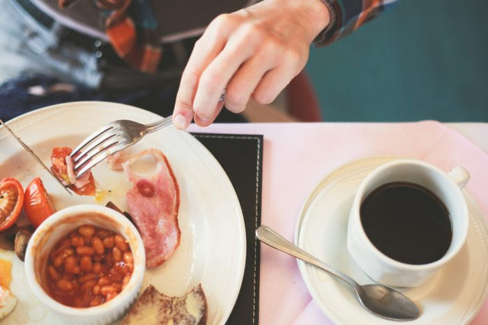 woman eating an English breakfast (beans, ham, tomatoes) and coffee