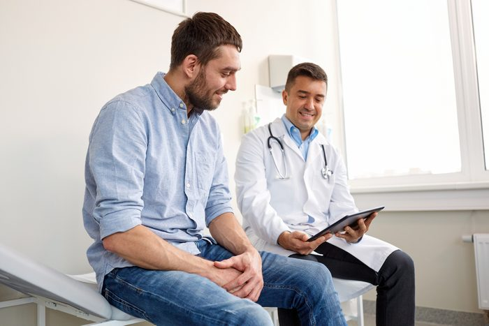 medicine, healthcare and people concept - smiling doctor with tablet pc computer and young man patient meeting at hospital