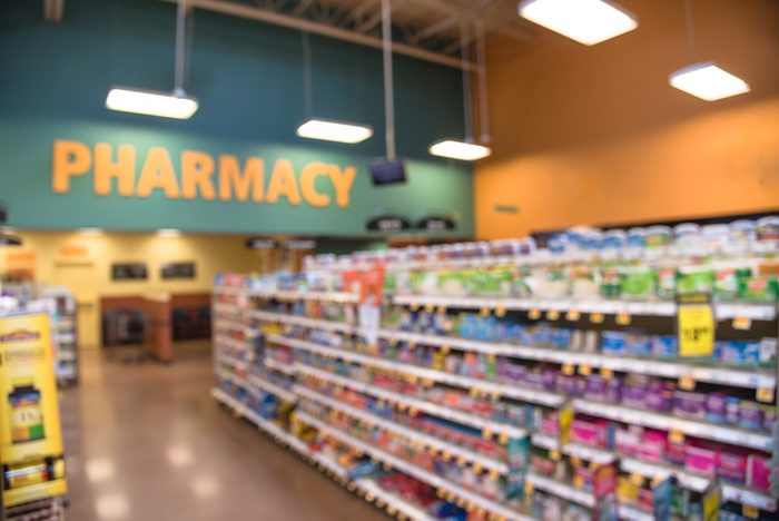 Blurred abstract background inside pharmacy store with arranged variation of pharmaceutical and medical supplies product in label on shelves display. Indoor space of drug store with blurred medicines.