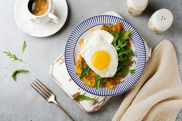 Fried egg with potato pancake, arugula and avocado