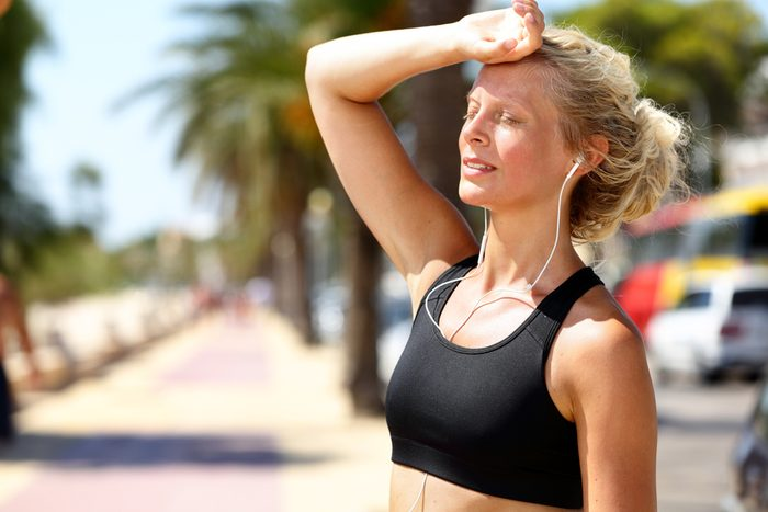 woman who is overheated, taking a break from outdoor exercise