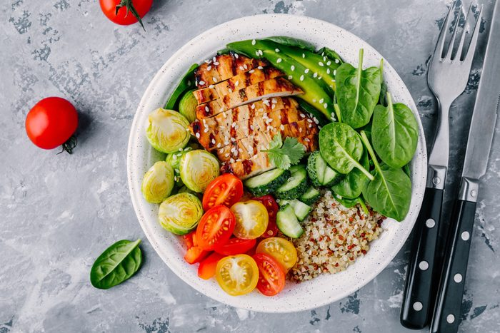 buddha bowl lunch with grilled chicken, quinoa, spinach, avocado, Brussels sprouts, tomatoes, cucumbers