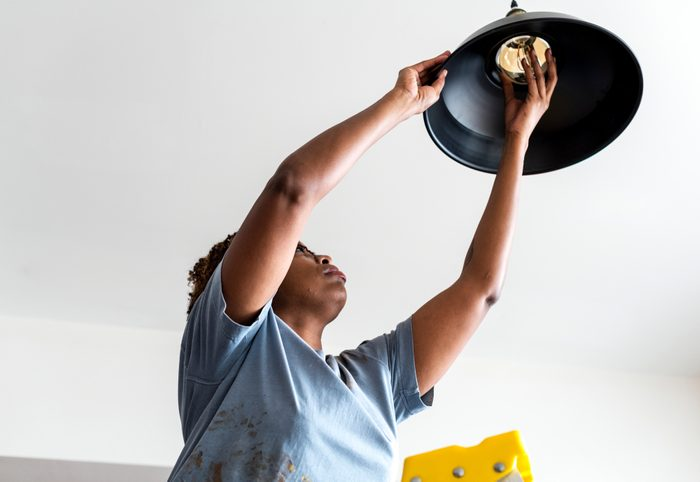 Woman changing lightbulb