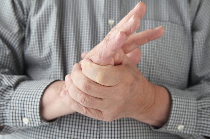 a man tries to restore feeling in his hand by squeezing
