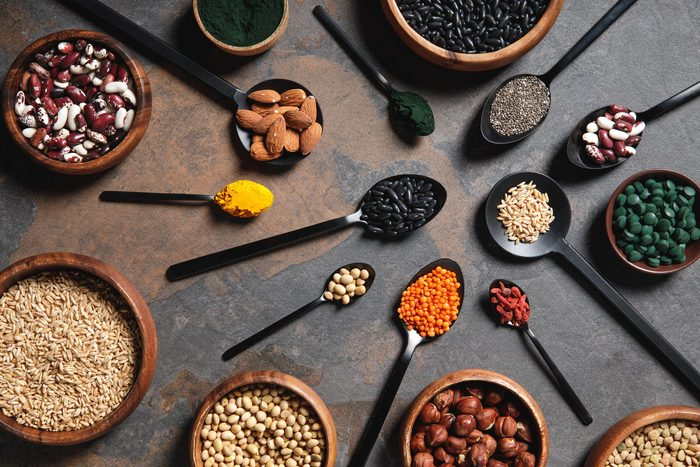 wooden bowls and spoons with superfoods, legumes and grains on table