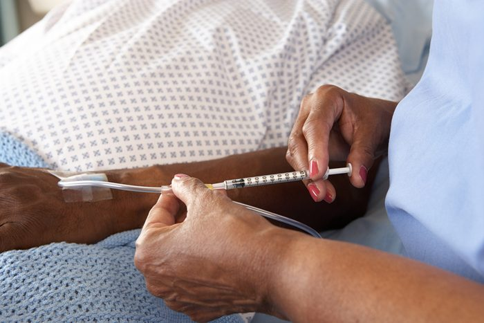 Nurse Injecting Patient's IV In Hospital Bed