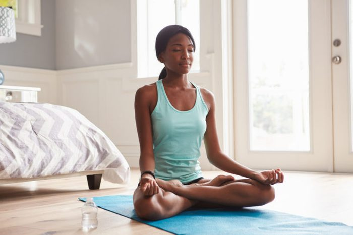 Young woman meditating at home in the lotus position