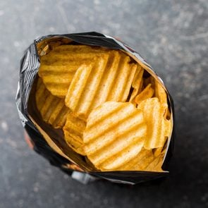 Crinkle cut potato chips on kitchen table. Tasty spicy potato chips in bag. Top view.