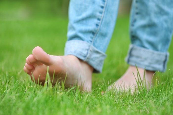 walking barefoot on green grass