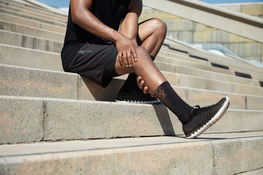 man holding leg in pain on steps