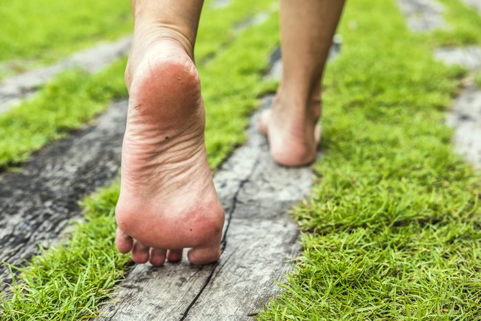 feet walking in grass and on old boards