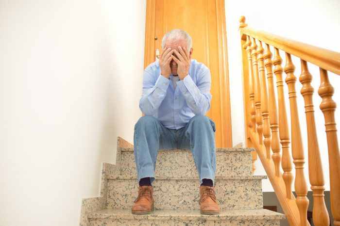 Senior man sitting on the stairs of home with his head in his hands