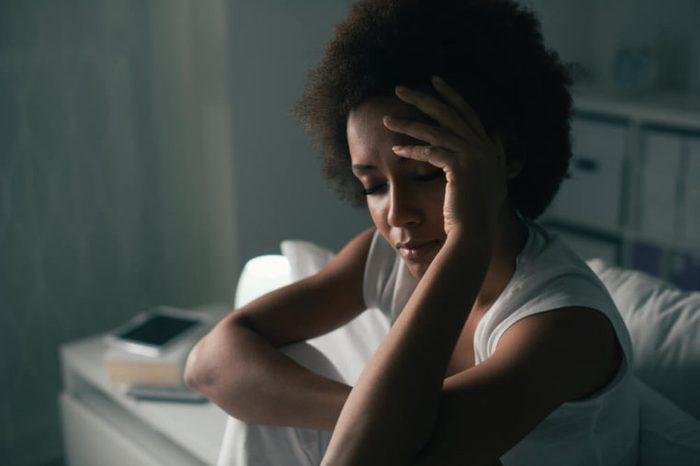Woman sitting up in bed with eyes closed, hand on head