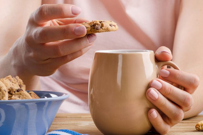 Female hands holding cup of tea and cookies