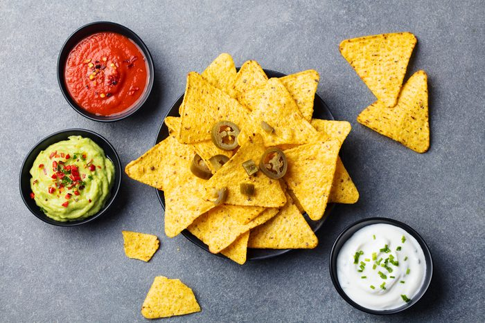 Nachos chips in bowl with sauces, dip variety