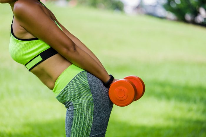 Young woman lifting a dumbbell behind her back