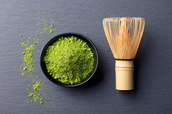 Matcha, green tea powder in black bowl with bamboo whisk on slate background. Top view.