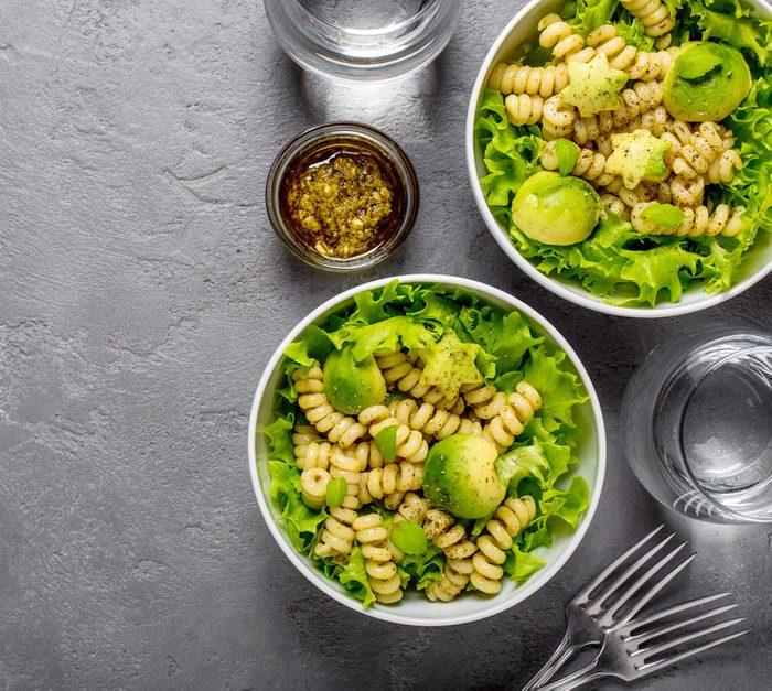 Two bowls of vegetarian healthy salad with macaroni pasta and pesto, avocado balls